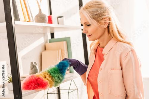 Leinwandbild Motiv Senior woman in rubber glove cleaning shelves with bright duster