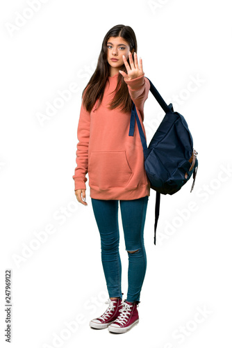 Leinwanddruck Bild A full-length shot of a Teenager girl with sweatshirt and backpack making stop gesture denying a situation that thinks wrong
