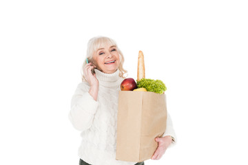 happy senior woman holding paper bag with groceries isolated on white