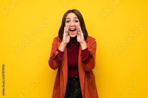 Leinwandbild Motiv Young woman with coat shouting and announcing something
