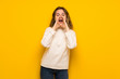 Leinwandbild Motiv Teenager girl over yellow wall shouting and announcing something
