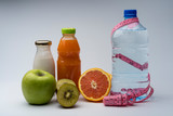 Female fitness still life. Healthy food, fruit, juice and water on grey background.