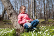 cute girl child brunette in a pink jacket in spring in the park with the first spring flowers on the lawn