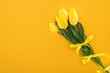 Leinwandbild Motiv top view of yellow tulip bouquet with ribbon on orange background for international women's day
