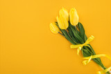 top view of yellow tulip bouquet with ribbon on orange background for international women's day - 247991107