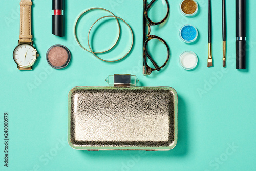 Top view of watch, lipstick, bracelets, glasses, eye shadow, blush, clutch, cosmetic brushes and mascara - 248000979
