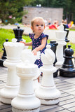 little baby girl playing giant chess