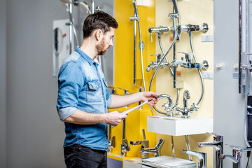 Man choosing shower faucet in the shop