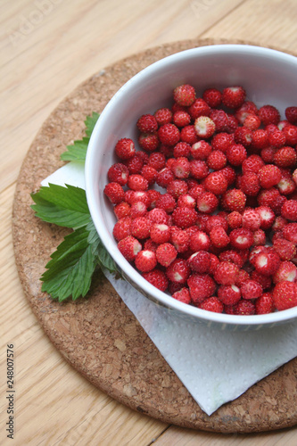 Foto Murales Fresh wild strawberries in a bowl on wooden table