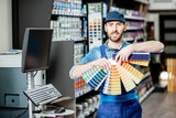 Portrait of a handsome workman with color swatches near the equipment for coloring in the building shop - 248008792
