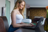 Young blonde woman typing on laptop indoors - 248009740
