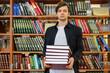 man in university holding stack of books (book shelf background) b