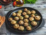 Fried, baked mushrooms in frying pan on wooden table