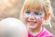 Leinwandbild Motiv Glückliches geschminktes Mädchen beim Kinderkarneval auf einem Freizeitpark mit einem weißen Luftballon
