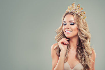 Smiling blonde woman with long curly hair, makeup and gold crown on background with copy space © millaf