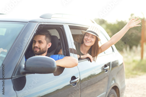 Happy couple traveling by car on the road in the summer - 248049567