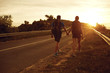 Travelers with backpacks go on the road  at sunset.