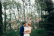 stylish bride and groom embracing and kissing in park among magnolia flowers. passionate luxury wedding couple hugging. romantic sensual moment.