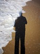 Shadow of a man on the sand at the seaside. Wave cover the shadow