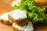 mini baguette sandwiches with cream cheese on the cutting board