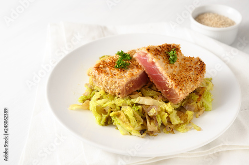 roasted tuna steak in sesame seeds with savoy cabbage vegetable, on a plate on a white table, copy space - 248062389