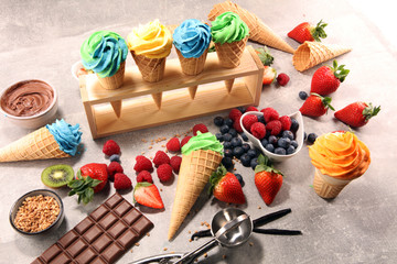 Vanilla frozen yogurt or colorful soft ice cream in waffle cone.
