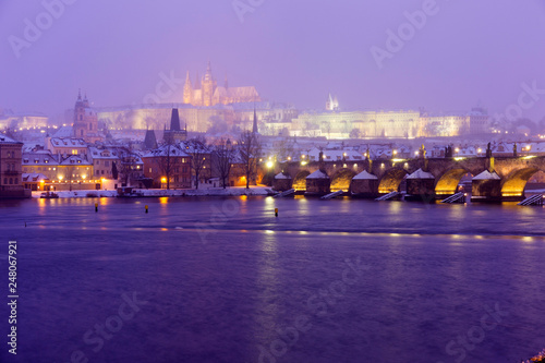 Foggy night Prague Lesser Town with gothic Castle, Bridge Tower and St. Nicholas' Cathedral in the Snowstorm, Czech republic