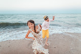 Children play and have fun on the beach. Loving teens. Romantic story on the seafront. The girl and the guy run away from the waves