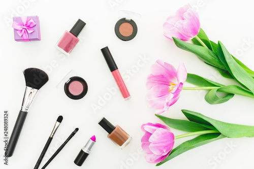 Leinwanddruck Bild - artifirsov : Beauty composition with pink tulips bouquet and cosmetics on white background. Top view. Flat lay.