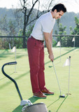 Man playing golf is going to hit ball at golf course