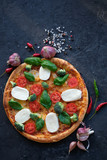 Italian pizza with Mozzarella cheese, tomatoes, broccoli, Spices and fresh basil. Pizza on black stone background