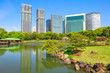 Hamarikyu Gardens with buildings reflecting on pond of Shiodome-Shimbashi District on background. Hama Rikyu is a large beautiful landscape garden in Chuo district, Sumida River, Tokyo, Japan.