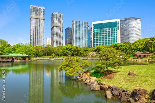 fototapeta na ścianę Hamarikyu Gardens with buildings reflecting on pond of Shiodome-Shimbashi District on background. Hama Rikyu is a large beautiful landscape garden in Chuo district, Sumida River, Tokyo, Japan.