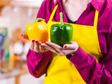 Woman holding two bell peppers - 248113560