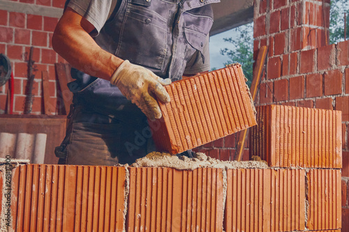 Real construction worker bricklaying the wall indoors. - 248117900