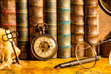 Antique clock on the background of vintage books. Mechanical clockwork on a chain. Fountain pen and glasses. - 248118395