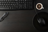 Total black desk with desktop and cup of coffee