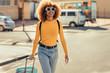 Cheerful woman traveller walking on street