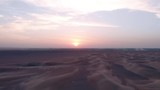 Aerial: Flying sideways while facing the sunset in the desert - 248129770