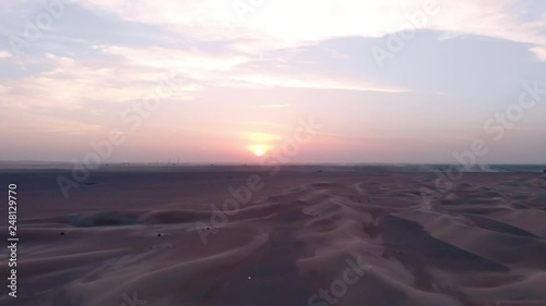 Aerial: Flying sideways while facing the sunset in the desert