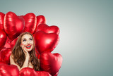 Beautiful woman with red balloons on banner background. Surprised girl, Valentine's day concept . Expressive facial expressions