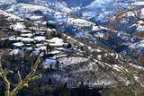 Small mountain village on a snowy slope with trees. Ancares Region, Lugo Province, Galicia, Spain. - 248140372