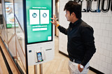 Indian man customer at store place orders and pay through self pay floor kiosk for fast food, payment terminal. Make a choise of language on screen. - 248141905