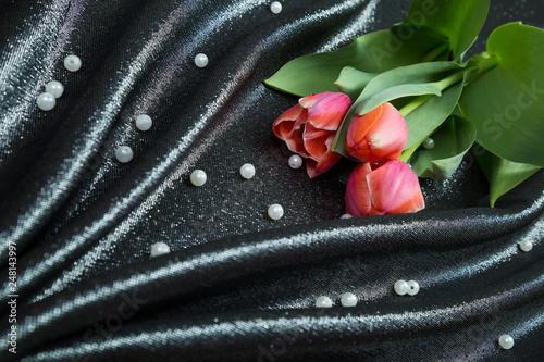 Foto Murales spring tender pink tulips on black brocade fabric