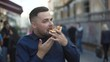 Happy man eats a piece of pizza with smile on face among the street