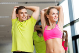sport, fitness, healthy lifestyle and people concept - smiling man and woman stretching in gym