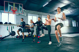 Shot of young men and women at the gym. Functional fitness workout. The group of people during training session. Fit athletic models. Healthy lifestyle concept
