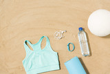 sport adn summer concept - sports top, mat, fitness tracker, earphones and water bottle on beach sand