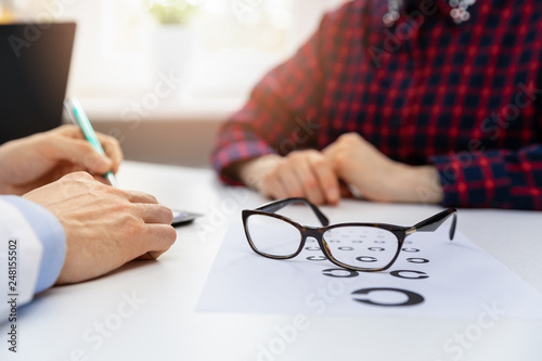 eye health - black glasses on eyesight test chart in optician office