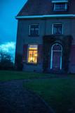 Illuminated window of house in twilight. - 248156500